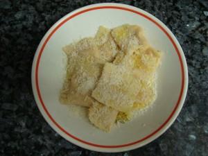 Ravilois de calabaza servidos en un plato, con un chorrito de aceite de oliva virgen y queso parmesano rallado